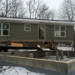 Modular home in the process of being craned off its carrier to be placed on a customers foundation