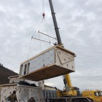 Modular home being craned off of its carrier to be set on its foundation