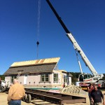 The roof of a modular home being lifted by the crane